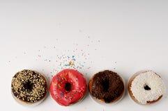 Donuts на плите на белой предпосылке Стоковое Фото