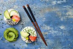 Donuts суш Vegan установили с замаринованными имбирем, авокадоом, огурцом, chives, nori и сезамом на голубой предпосылке тенденци Стоковые Изображения