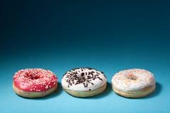 3 donuts с замороженностью цвета на голубой предпосылке Стоковые Изображения RF