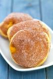 Donuts с сливк на белом блюде на голубой предпосылке Стоковые Фото
