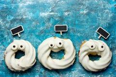 Donuts хеллоуина в белом шоколаде с глазами сформировали пугающее на b Стоковые Фото