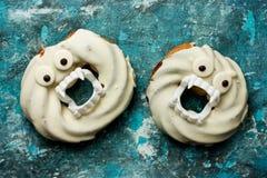 Donuts хеллоуина в белом шоколаде с зубами и глазами на сини Стоковая Фотография RF