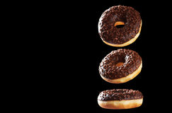 Donuts шоколада в движении изолированные на черноте Стоковые Фото