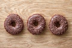 3 donuts шоколада на деревянной деревенской таблице Стоковое Изображение