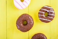 Donuts шоколада на желтой предпосылке Стоковая Фотография