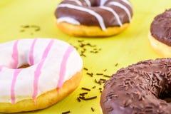Donuts шоколада на желтой предпосылке Стоковые Фото
