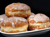 Donuts. Polish donuts with icing over black background Royalty Free Stock Photo
