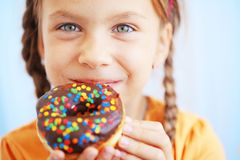 Donuts. Cute kid girl eating sweet donuts Stock Images