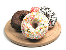 Donuts. A couple of donuts on a wooden plate Stock Photos