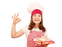 Кашевар маленькой девочки с donuts и одобренная рука подписывают Стоковое Изображение