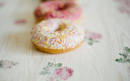 Three donuts on a background in the style of a shabby chic. Donuts on a background in the style of a shabby chic. Wooden light background with flowers stock photography