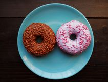 Donuts on the blue plate on the wooden table royalty free stock photography