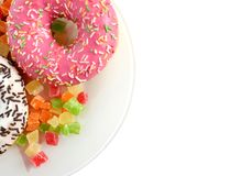 Donuts and bright colored pineapple slices on a plate of isolate royalty free stock images