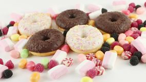 Donuts and bright sweet candies and marshmallows stock footage