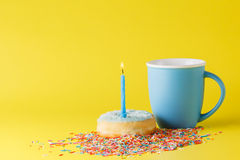 Donuts on brigth background with blue mug. Fun birthday donut with candle on brigth yellow background Stock Photography