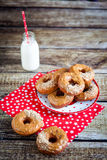 Donuts with caramel and nuts. On plate, red fabric with stars and wood background. Milk in a small bottle and red straw with white stars Royalty Free Stock Photography