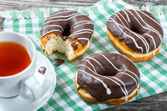 Donuts with Chocolate Icing, a cup of tea, top view Royalty Free Stock Image