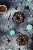 Donuts with chocolate and macaroons on a dark background Stock Photo