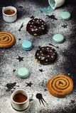 Donuts with chocolate and macaroons on a dark background Stock Images