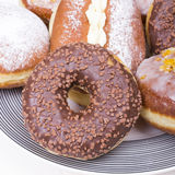 Donuts with chocolate on the platter Royalty Free Stock Photography