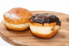Donuts with chocolate and vanilla on the wooden board Royalty Free Stock Images