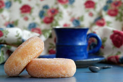 Donuts and coffee. Close-up of donuts on a blue table with a coffee cup on the background Stock Photos