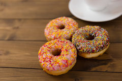 Donuts and coffee cup on wood table. Iced donuts on wood table royalty free stock photography