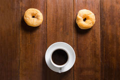 Donuts and Coffee cup on wooden background, top view Royalty Free Stock Image