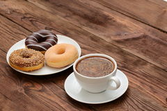 Donuts and coffee. Sweet donuts with aromatic coffee at any free time is worth a try Stock Photos