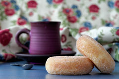 Donuts and coffee. Two donuts placed on a blue table with a handmade coffee cup in the background Stock Photos