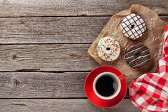 Donuts and coffee on wooden table Royalty Free Stock Images