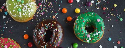 Donuts and colorful sprinkles. On dark stone background, Party, Selective focus Royalty Free Stock Photography