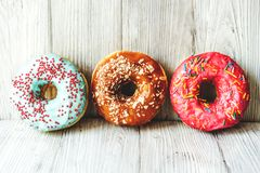 Donuts covered with multicolored glaze stock images