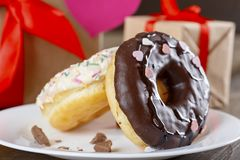 Donuts for St.Valentine`s Day on the background of gifts. Donuts on a dark wooden table on the background of gifts. Happy Valentine`s Day Royalty Free Stock Photography