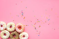 Donuts decorated icing and sprinkles on pink background top view copy space pattern. Donuts decorated icing and sprinkles on pink background top view pattern stock photo