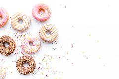 Donuts decorated icing and sprinkles on white background top view copy space pattern.  royalty free stock image