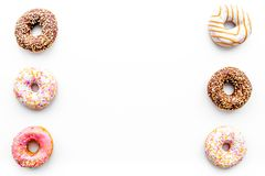 Donuts decorated icing and sprinkles on white background top view copy space pattern.  stock photography