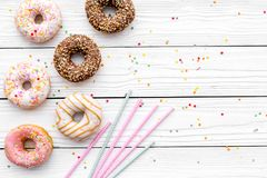Donuts decorated icing and sprinkles on white background top view copy space space for text. Donuts decorated icing and sprinkles on white background top view stock photography