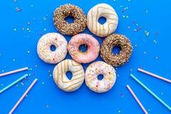 Donuts dekorowali lodowacenie i kropią na błękitnej tło odgórnego widoku kopii przestrzeni przestrzeni dla teksta Obrazy Stock