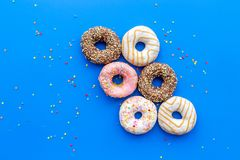 Donuts dekorowali lodowacenie i kropią na błękitnej tło odgórnego widoku kopii przestrzeni przestrzeni dla teksta Zdjęcie Stock