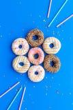Donuts dekorowali lodowacenie i kropią na błękitnej tło odgórnego widoku kopii przestrzeni przestrzeni dla teksta Obrazy Royalty Free