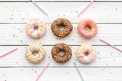 Donuts dekorowali lodowacenie i kropią na białej tło odgórnego widoku kopii przestrzeni przestrzeni dla teksta Zdjęcia Royalty Free