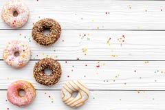 Donuts dekorowali lodowacenie i kropią na białej tło odgórnego widoku kopii przestrzeni przestrzeni dla teksta Obraz Royalty Free