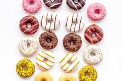 Donuts of different flavors for breakfast on white background top view stock photos