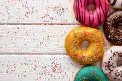 Donuts in different glazes on wooden background and space for text. Donuts in different glazes on wooden white background and space for text Royalty Free Stock Photo