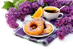 Donuts en oranje thee met bloemen van sering voor ontbijt op w Stock Foto's