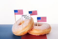 Donuts with Flags and Happy 4th of July. Donuts with Flags and a Banner with Happy 4th of July royalty free stock photos