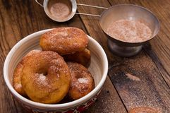 Donuts flavored with cinnamon, nutmeg and powdered. Sugar on a wooden table Stock Photography