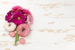 Donuts and gerbera flowers bouquet Stock Image