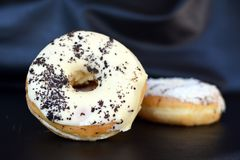 Donuts glazed with white chocolate and cookie crumble sprinkles as topping stock photography